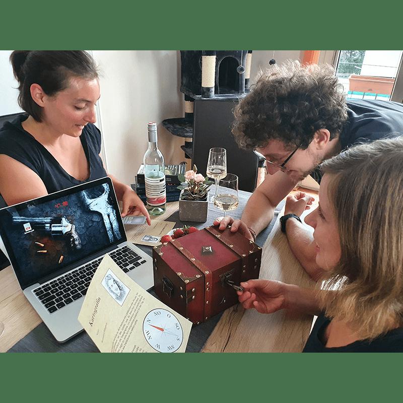 Drei Spieler stehen um einen Tisch herum, auf dem ein Laptop, eine verschlossene Truhe und eine Weinflasche mit Gläsern steht und diskutieren.