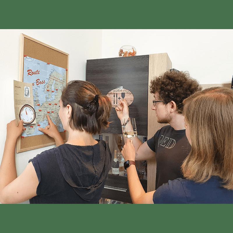Drei Spieler betrachten eine große Landkarte an einer Wand und ein Bild mit einem Besteck und einem Glas abgebildet.