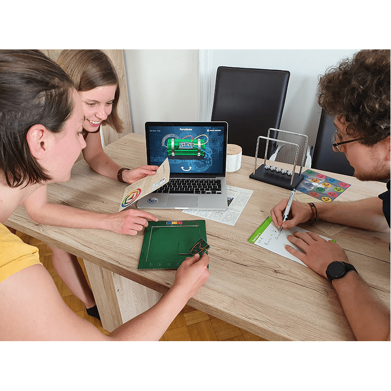 Drei Spieler stehen um einen Tisch herum, auf dem ein Laptop mit einer abgebildeten Bombe steht und machen sich Notizen. Einer der Spieler hält ein Puzzleteil mit Kabeln in der Hand, ein anderer einen Steckbrief.