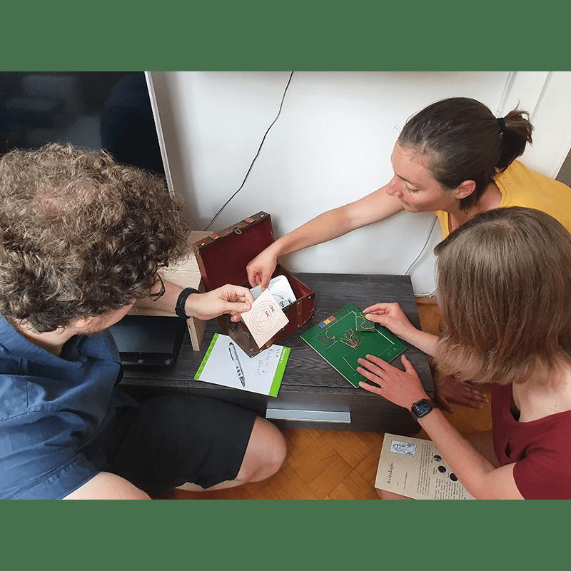 Drei Spieler knien vor einer offenen Truhe und betrachten den Inhalt. Einer der Spieler versucht ein Puzzle mit Kabelteilen zu lösen.