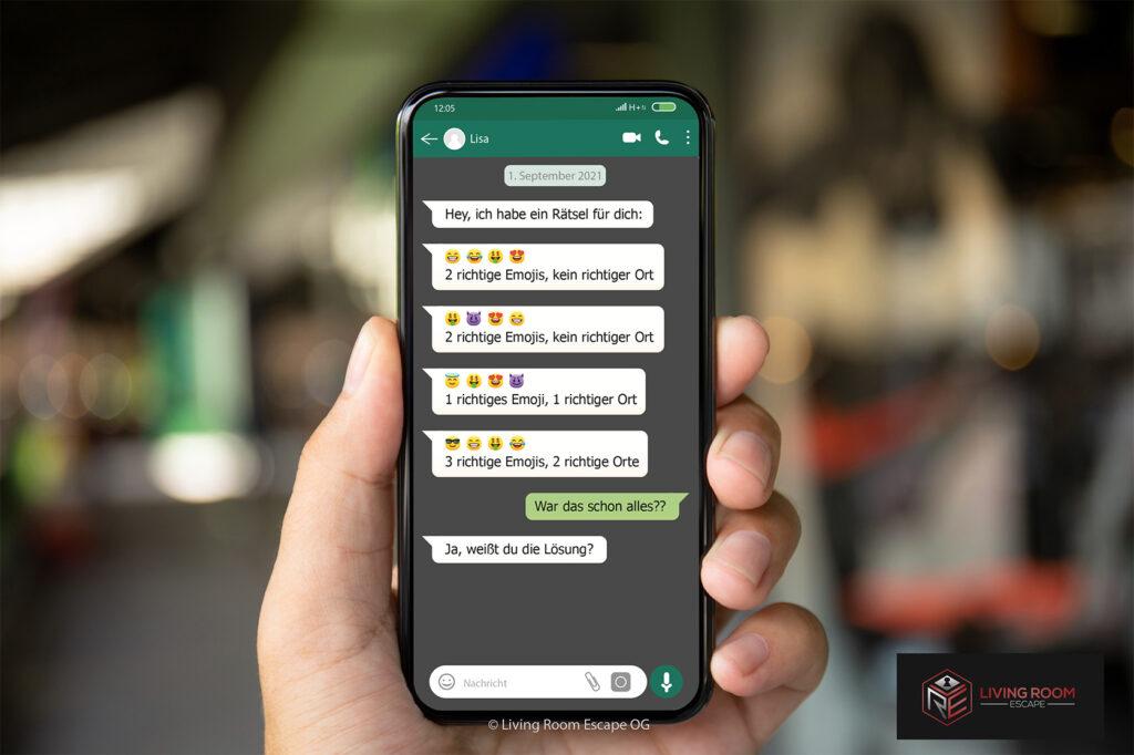 Hand, die ein Smartphone mit Chatverlauf über ein Rätsel mit Emojis hält.